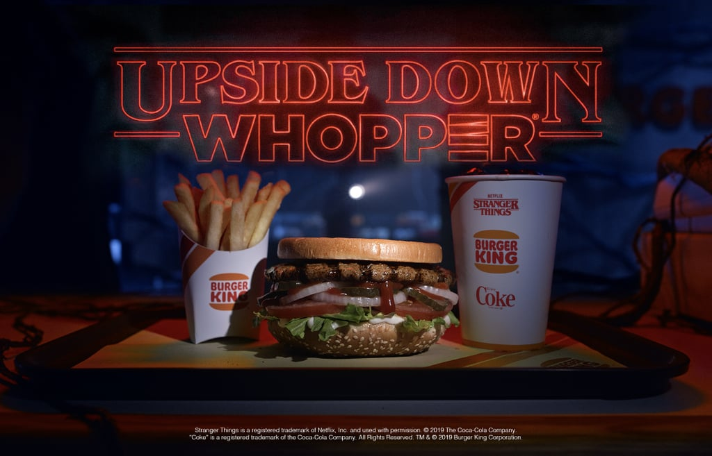 """Burger King is ready for the return of Stranger Things — are you? In honor of season three of the sci-fi series premiering on July 4, the fast-food joint teamed up with Netflix and Coca-Cola to give all Hawkins fans a special treat. On June 21, select Burger King restaurants will be serving an Upside Down Whopper and more limited-edition items for the hungry Demogorgon in all of us. Select locations will also offer ketchup packets that look like Eleven's bleeding nose, """"crowns"""" that resemble Dustin's hat, and t-shirts inspired by the Stranger Things crew.  Since we know you're wondering: yes, the Upside Down Whopper has the same ingredients as Burger King's staple menu item, except it's literally flipped upside down. Check out the delicious (and slightly creepy) limited-edition Stranger Things items at Burger King ahead.      Related:                                                                                                           6 New Stranger Things Season 3 Theories That Just Might Flay Your Mind"""