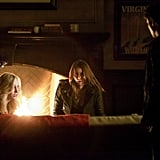 Caroline (Candice Accola) relaxes (ha, not really) by the fire with Elena.