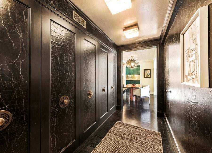 Guests enter through a hallway lined with beautiful (and storage-creating) closets coated in hand-troweled plaster and finished with a leather-like effect.
