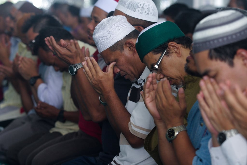 Men in Kuala Lumpur, Malaysia, prayed for the missing passengers on Friday.
