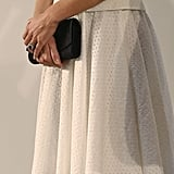 Her simple black clutch doesn't take away from the subtle texture of her Alexander McQueen outfit.