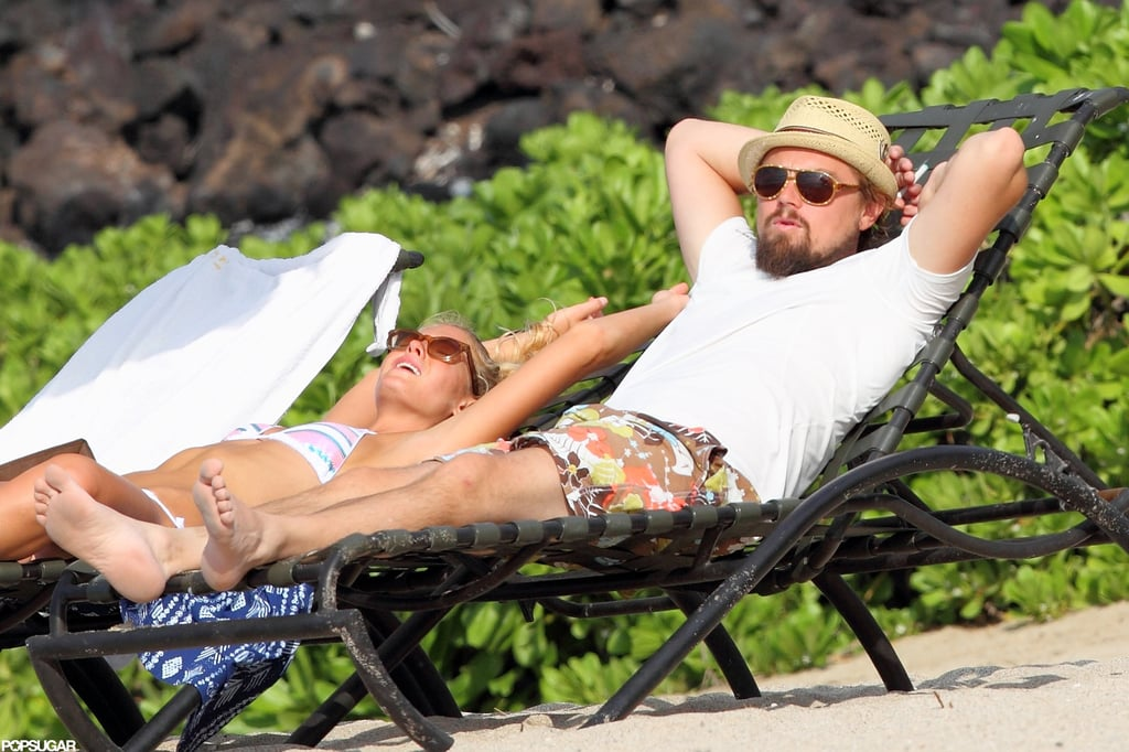 Leonardo DiCaprio sunbathed in a t-shirt next to girlfriend Erin Heatherton in Hawaii in July 2012.