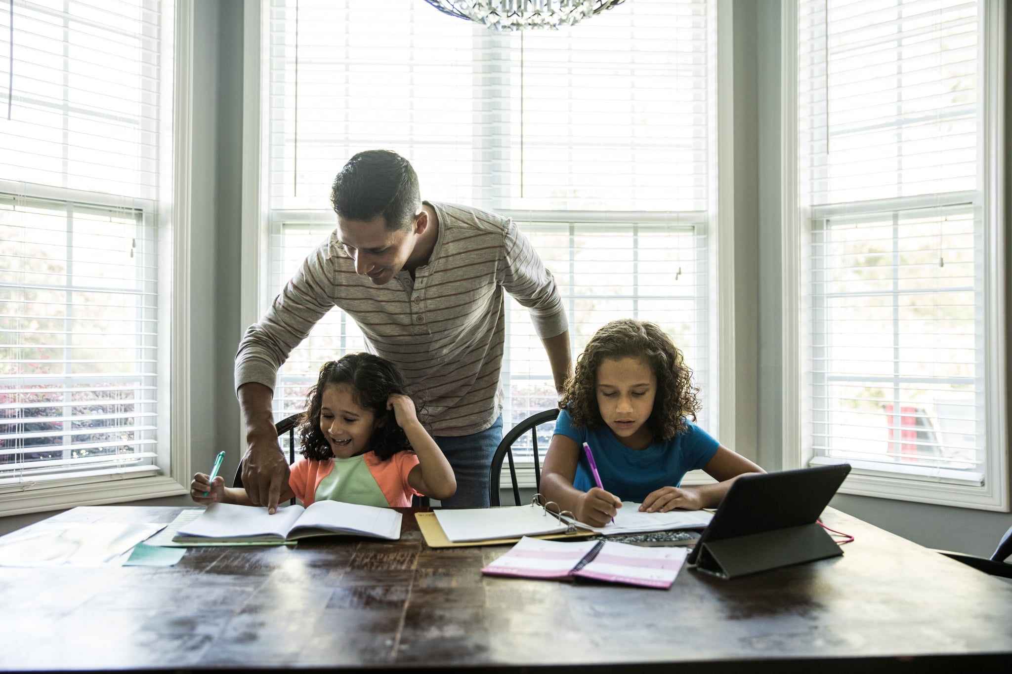 Father helping young girls with schoolwork at kitchen table