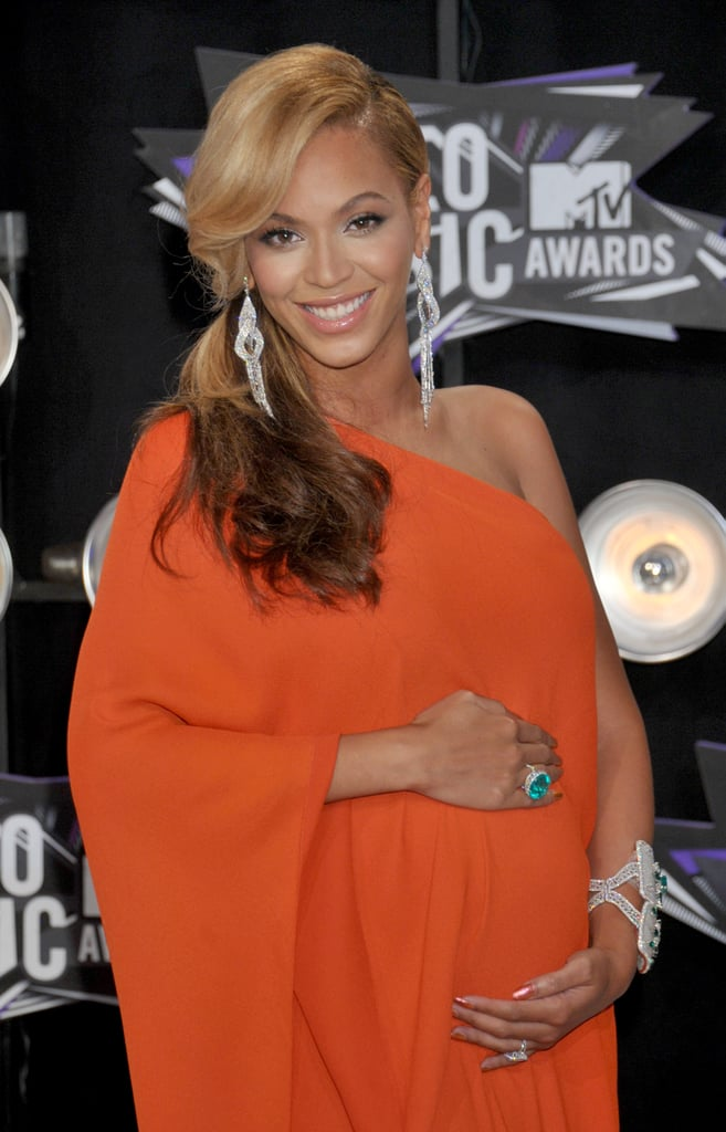 2011: Beyoncé hit the red carpet in a loose-fitting orange gown, clutching her growing baby bump.
