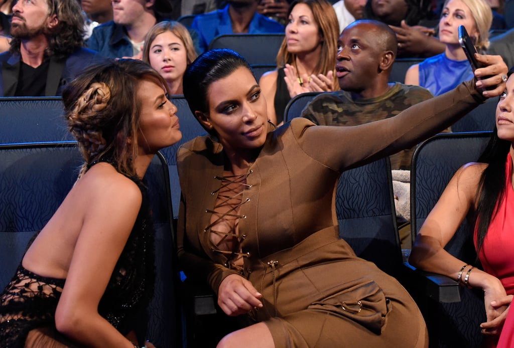 Chrissy Teigen and Kim Kardashian snapped selfies in the audience in 2015.