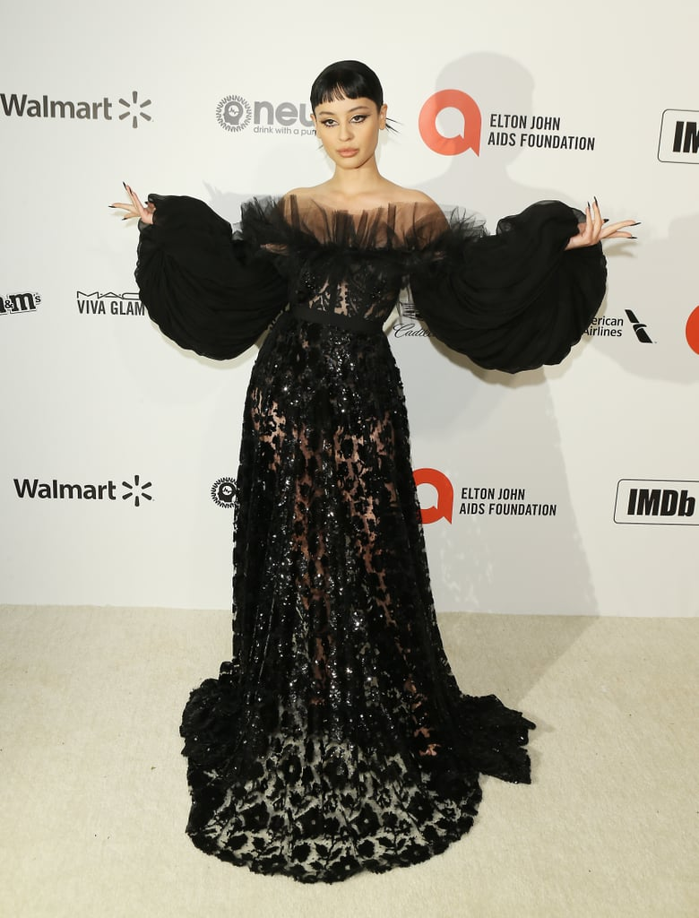 Double, double, toil and trouble — Alexa Demie cast a spell on the red carpet at the 2020 Oscars on Sunday in this wicked ensemble that would leave Maleficent trembling with envy. The translucent Giambattista Valli gown features an embroidered floral design, a ruched chiffon collar, and sleeves so big even Billie Eilish isn't sure who's really that puff guy — so consider me absolutely spellbound. The Euphoria star paired her gorgeous look with a spiked bun, a razor-sharp cat eye, and a black french tip manicure. As enchanting as the dress is on its own, its the severe styling that pulls the whole look together and has me hoping to see her in a Maleficent sequel. Check out Alexa's full look from all angles ahead, and prepare to be transfixed.       Related:                                                                                                           Is It Just Us, or Does Tracee Ellis Ross Literally Look Like a Shiny Oscar Award?