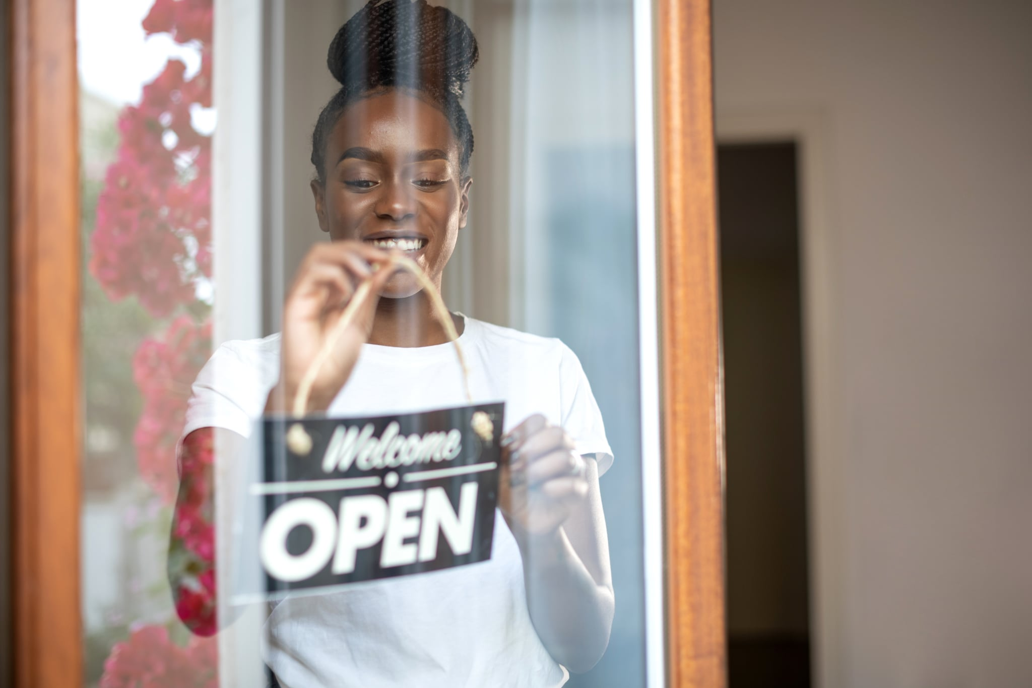 Afro american woman holding open sign in a small business shop after Covid-19 pandemic.