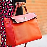 A vibrant orange satchel popped against bright animal prints.