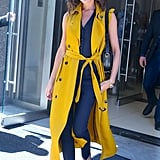 Wearing a long yellow trench vest and jumpsuit in June 2016.