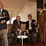 Roger chats up a flight attendant while Bert Cooper (Robert Morse), Jim Cutler (Harry Hamlin), and Ted (Rahm) talk.