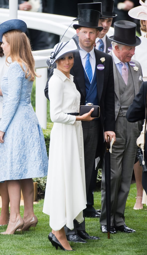 To accessorize her stunning outfit, Meghan opted for a black clutch, matching heels, and a black and white hat by Philip Treacy.