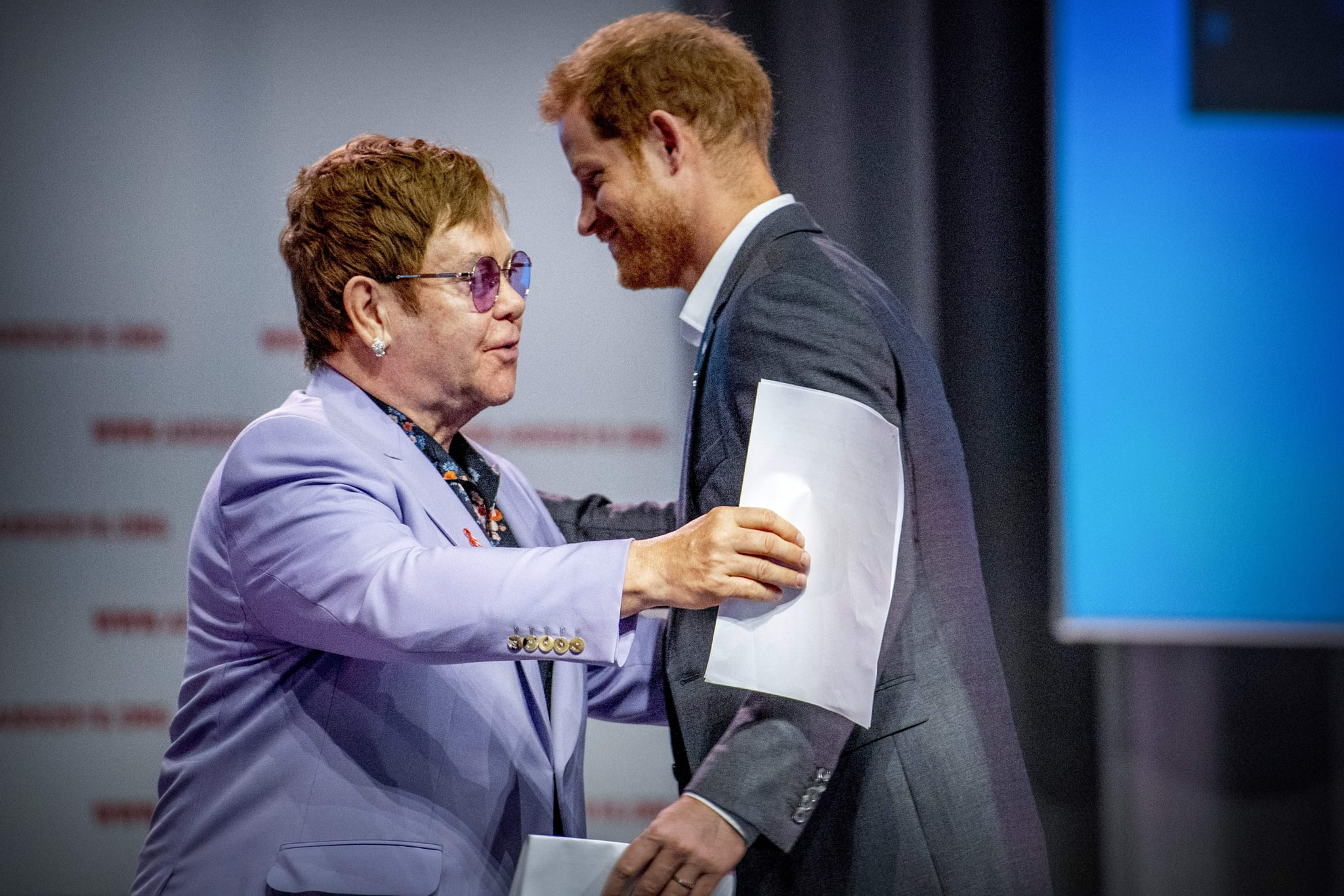 British Prince Harry (L) and sir Elton John attend a session about the Elton John Aids Fund on the second day of the Aids2018 conference, in Amsterdam on July 24, 2018. - From 23 to July 27, thousands of delegates -- researchers, campaigners, activists and people living with the killer virus -- attend the 22nd International AIDS Conference amid warnings that