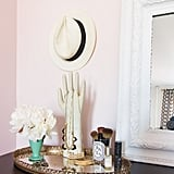 Small spaces require extra organization. A tray is the perfect place to store jewelry, makeup, and other knick-knacks so they don't overwhelm the top of the dresser, making the entire room feel cluttered. We love the stylish way this apartment-dweller hung her jewelry on a glove mold and stored makeup brushes in a repurposed candle jar.