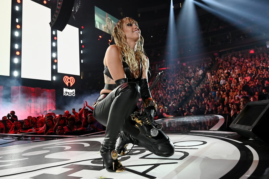 "Miley Cyrus isn't letting a breakup stop her from rocking out! At Saturday's iHeartRadio Music Festival in Las Vegas, the 26-year-old singer delivered a power-packed performance that included the live debut of her single ""Don't Call Me Angel."" Although the track's other vocalists, Ariana Grande and Lana Del Rey, weren't able to join, Miley boldly commanded the stage. Clad in a black leather ensemble, she also sang her songs ""Nothing Breaks Like a Heart"" and ""Slide Away."" She then switched things up, paying homage to classic rock hits, such as Pink Floyd's ""Comfortably Numb"" and Led Zeppelin's ""Black Dog."" Backstage, Miley even snapped a few pictures with legendary rock band Def Leppard, who also performed at the festival. ""Stoked to have shared the same stage with the legends themselves!"" she captioned a clip of her enjoying their set. ""We talked about doing some shows together! F*ck yes! Let's do it!"" Miley's high-energy concert comes shortly after news of her and Kaitlynn Carter's breakup made headlines. The two first developed a romance in August, following their respective splits from husbands Liam Hemsworth and Brody Jenner. But in September, they amicably ended their relationship. ""They're still friends,"" a source told People. ""They've been friends forever and were there for each other when they were both getting separated, but they're just not in a romantic relationship anymore."" Keep scrolling to see more photos and videos from Miley's iHeartRadio appearance!      Related:                                                                                                           10 Times Musicians United on Stage This Year For a Phenomenal Performance"
