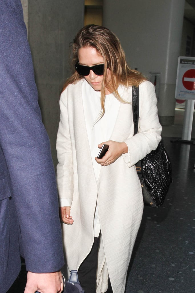 Mary-Kate accented her long, white travel coat with black accessories at LAX in 2016.