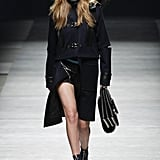 Gigi worked a structured navy and black coat with edgy cutouts and hardware. Her outfit was complete with a satchel, zippered booties, and a headwrap.