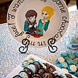 Anna strategically placed decorative plates near appropriate party foods. This adorable piece displays a quote about chocolate, so she arranged it next to the chocolate cookies.