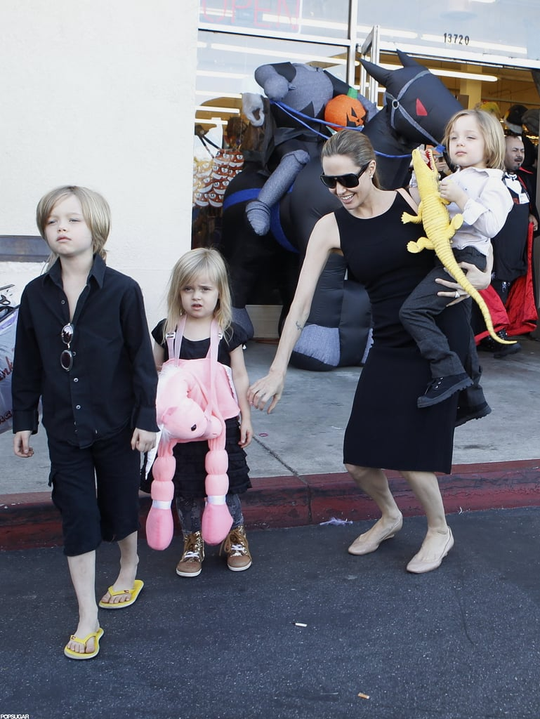 Angelina Jolie carried Knox on her hip as she made her way out of a Halloween store in LA with Vivienne and Shiloh in October.