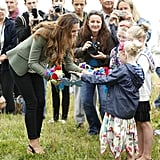 While visiting locals in Holyhead, Wales in August 2013, Kate was given posies.