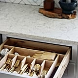 Drawer organizers keep flatware and other tools in order. How pretty is that gold flatware?