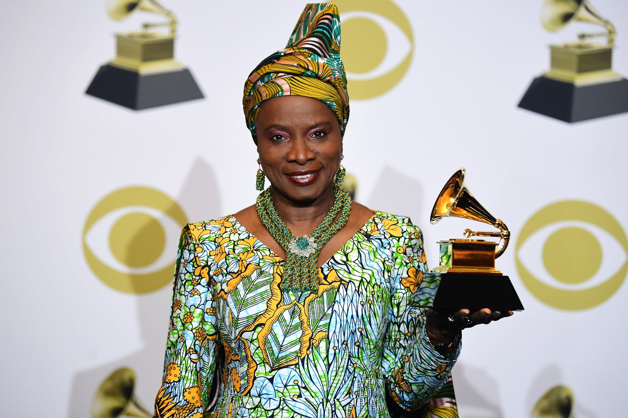 Beninese singer-songwriter Angelique Kidjo poses in the press room with the award for Best World Music Album for