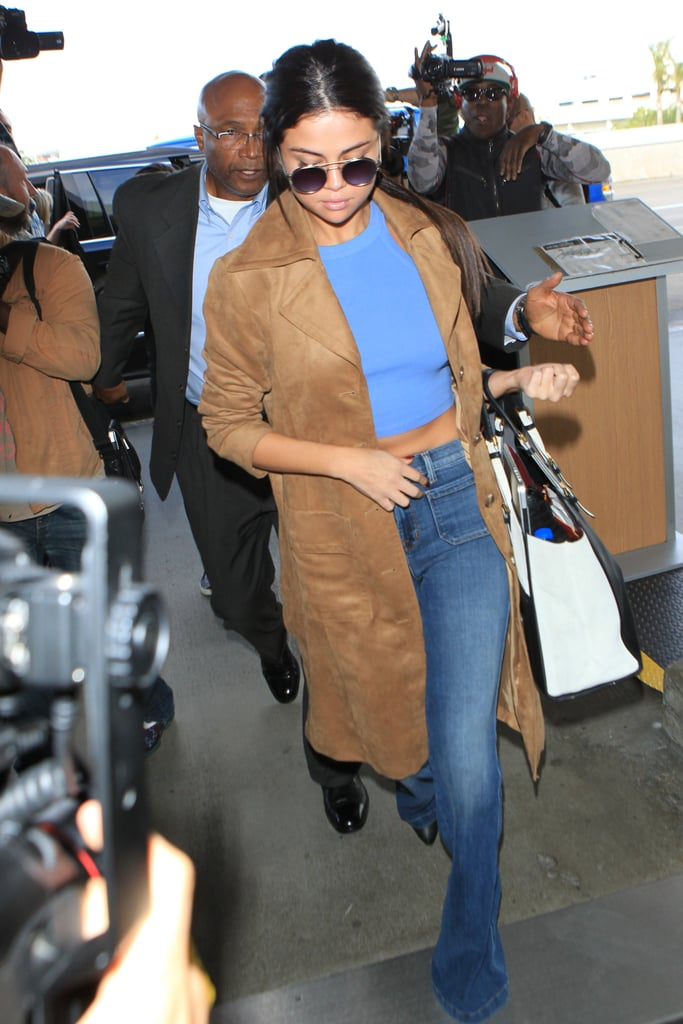 Fall staple: a neutral suede trench by H&M. Selena wore it with: Blue separates, including flared J Brand denim and an Urban Outfitters tank, plus Simon Miller sunglasses and a Louis Vuitton tote, at LAX in November 2015.