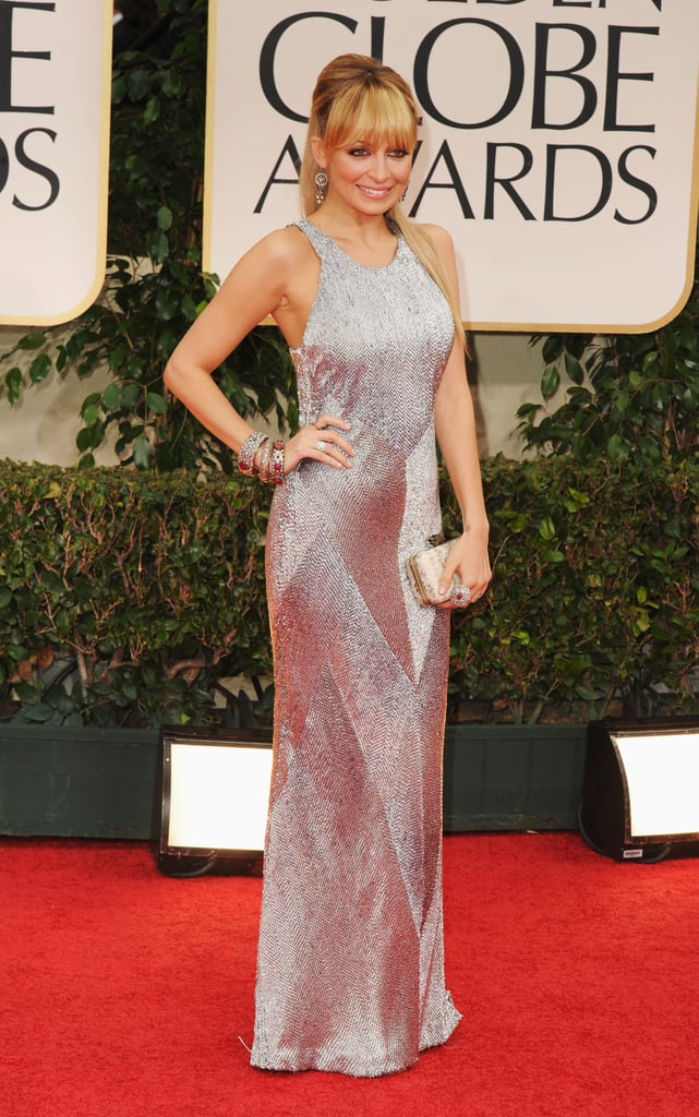Nicole Richie hit the Golden Globes red carpet in LA this evening wearing a chic silver gown from Julien Macdonald. She paired it with a House of Harlow bag! The mom of two, who will show off her own design skills in the upcoming reality TV show Fashion Star, was one of the first to arrive for the show. Nicole's having a glam night, but her husband Joel Madden started the day in a little more low-key manner. Joel tweeted about enjoying crab cakes and football a few hours ago! He was actually the in-house DJ for the 2011 Oscars, but it seems he might be skipping out on the proceedings tonight. Weigh in on Nicole's look and more with our Golden Globes beauty and fashion polls!
