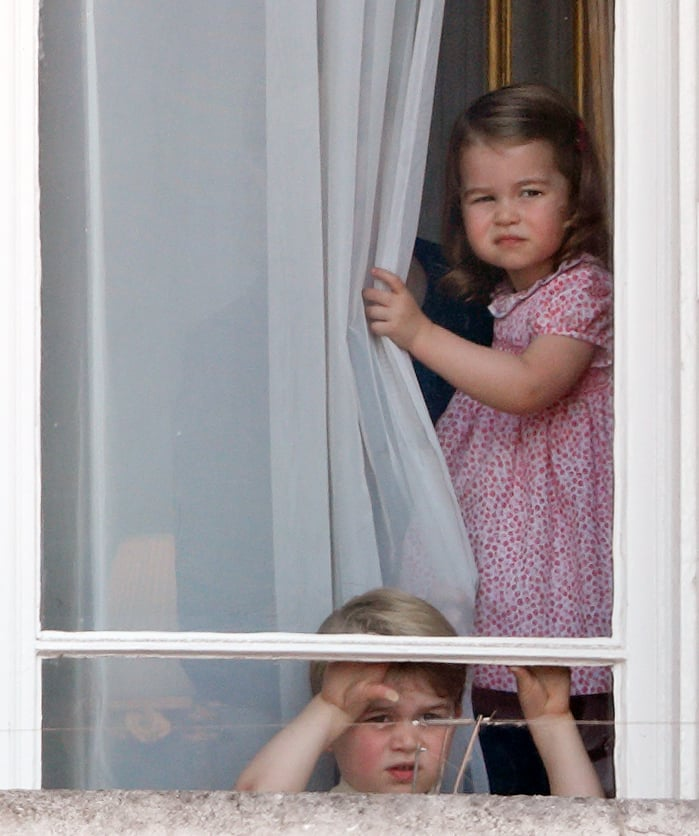 Before heading out to the balcony of Buckingham Palace for the Trooping the Colour, Princess Charlotte and Princess George skeptically investigated the scene from a palace window.