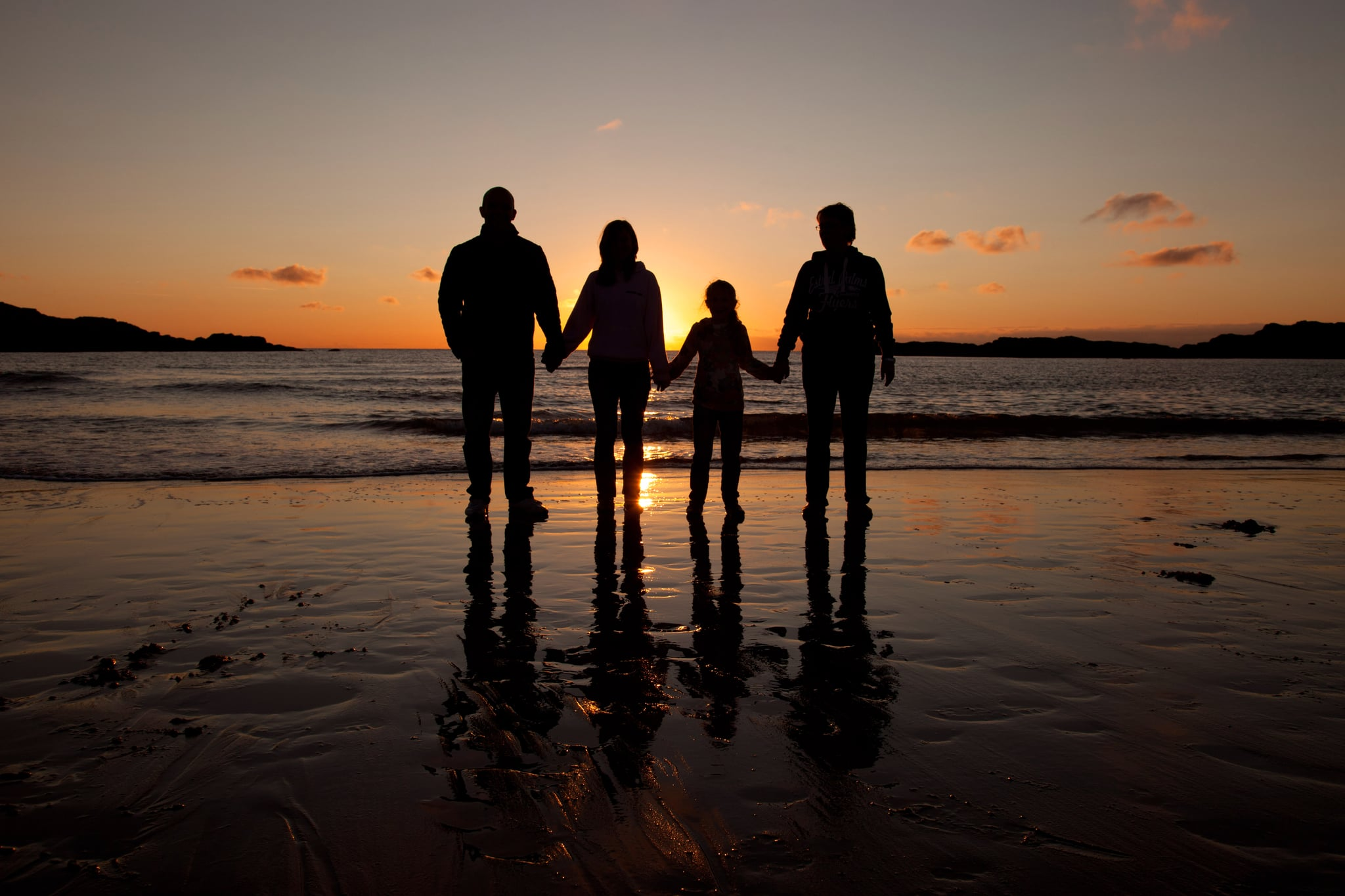 Family in sunset at Trearddur Bay on Isle of Anglesey.