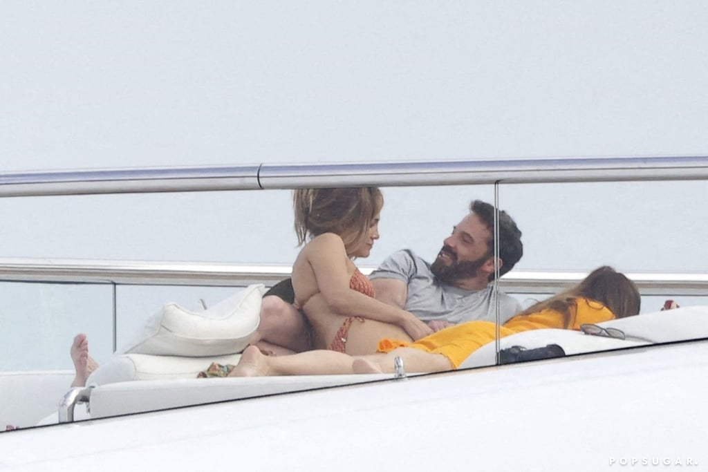"""Whether it's packing on the PDA in Malibu or a quick getaway in the Hamptons, we're never quite sure what to expect from Jennifer Lopez and Ben Affleck lately. In celebration of the singer's 52nd birthday on July 24, the couple took things back to 2002 with a steamy real-life re-creation of their iconic """"Jenny From the Block"""" video. In the photos, Ben could hardly keep his hands to himself as they shared an intimate kiss. With a cheeky look toward the paparazzi, it's clear Ben and Jen have a sense of humour about things.  Ironically, the theme of the original 2002 music video was about the interest surrounding Jen and Ben's relationship at the time. Guess the video is still a fond memory for both; according to People, while partying at L'Opéra in St.-Tropez, """"the couple got cosy in a booth as they sang along to her 2002 single 'Jenny from the Block.'"""" You can compare pictures from their holiday and the sexy music video ahead.      Related:                                                                                                           Jennifer Lopez and Ben Affleck Are Proof That Sometimes Love Is Worth a Second Chance"""