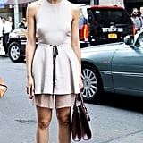 Caroline Issa perfected the easy, modern feminine vibe in a neutral drawstring tunic, flats, and standout sunglasses.