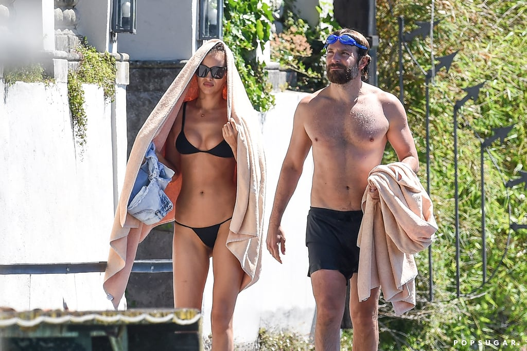 Less than a week after taking Wimbledon by storm, Bradley Cooper and Irina Shayk escaped to Garda Lake in Italy for some quality R&R. On Saturday, the couple — who have been going strong for a little over a year now — were seen soaking up the sun by the lake. Bradley went shirtless and donned some bright orange board shorts, while Irina flaunted her fit bikini body in a sexy yellow two-piece and had tin foil wrapped around her head — perhaps she was dying her hair? On Tuesday, the couple was back in the water for a swim, and Irina was in a black bikini for more time in the sun. Most recently, the duo grabbed headlines after a video surfaced of what looked like the pair fighting in the stands at Wimbledon. While neither Bradley nor Irina addressed the rumors, judging by these photos, all is well between the two lovebirds.