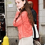Katie Holmes wore a red jacket on a Summer day.