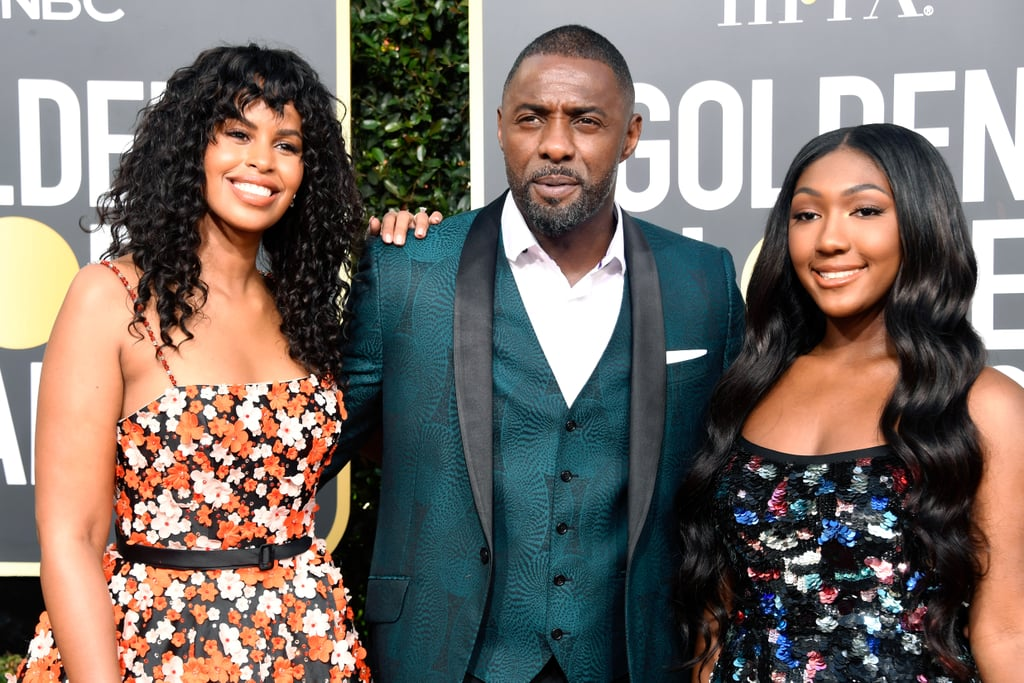 """If you thought money was the only reason to love the color green, Idris Elba is here to enlighten you. The 46-year-old actor — and DJ, if you still haven't learned that tidbit — blessed the 76th Annual Golden Globes red carpet alongside his fiancée, Sabrina Dhowre, and his daughter, Isan Elba. Sporting a patterned green suit jacket with matching waistcoat and his usual roguishly charming smile, the Sexiest Man Alive looked like he was living his best life on the red carpet. Isan, who serves as this year's Golden Globes Ambassador, continues to prove that her father doesn't have all the good looks in the family, and to top it all off, Sabrina has us dreaming of fields and fairies in the best possible way.  Before they walked the carpet, Idris revealed that he had been giving his daughter advice for her Ambassador duties, including the evergreen tip that """"elegance is presence."""" Clearly, Isan has taken note. Check out the gorgeous trio working the Golden Globes red carpet ahead!"""