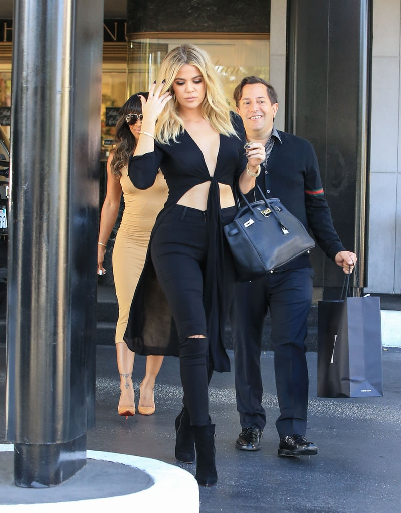 """Khloé Kardashian gave a glimpse of her toned stomach while out on a shopping trip in LA on Monday. The reality TV star strutted her stuff in black jeans and a knotted top and put her enviable figure front and center while heading back to her car. Khloé got real about her fitness routine in a stunning spread for Harper's Bazaar this week; the 31-year-old, who recently made headlines when it was reported that she would be once again filing for divorce from estranged husband Lamar Odom, opened up about her 40-pound weight loss, saying that the stress of their """"depressing"""" marriage is what motivated her to hit the gym. """"My home [with Lamar] was dark and toxic,"""" she said, adding that she started going to the gym because """"they had a TV and I could watch the Real Housewives on an elliptical. No one talked to me. I loved that solitude."""" In addition to serving fashion-forward looks for Harper's Bazaar and on the streets of Los Angeles, Khloé also gave back recently by serving free ice cream from a Coolhaus truck in promotion of her new apps. In between scooping snacks for the crowd, she stopped to take a few selfies and happily chatted with fans."""