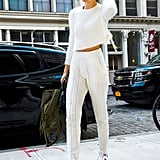 The model kept her white fuzzy sweater and knitted joggers outfit casual with a Yankees hat and Adidas sneakers.
