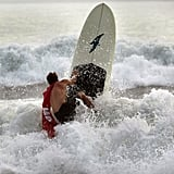 A surfer in Kitty Hawk, NC, takes advantage of the extreme waves brought on by Hurricane Irene ahead of the expected storms.