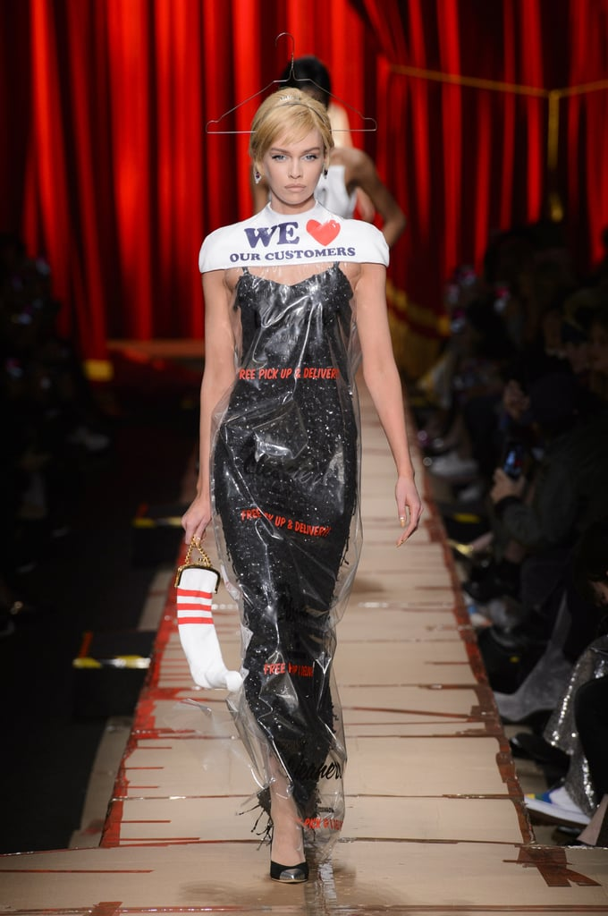 "Our takeaway from the Moschino Fall 2017 show? One person's junk is another person's treasure. Jeremy Scott transformed ordinary items — bubble wrap, UPS boxes, magazine cutouts, trash lids — into wearable runway looks. The first set of models wore beige dresses, tops, and shirts inspired by the packages we use (and toss out) every day. Words like ""fragile"" and ""caution"" were splashed across the clothes, while small boxes doubled as hat fascinators to drive home the point.   ""Yes, we totally see where this is going,"" we thought as Kendall Jenner and Gigi and Bella Hadid walked out in similar looks. The designer had appeared to use the post office as inspiration. But folks, that wasn't all. Jeremy still had plenty of magical creations up his sleeves, including dry-cleaning bags turned into dresses, duct-taped gowns, and hip-hop-influenced outfits. Models went from having '60s-inspired haircuts to wearing oversize gold medallions and colorful snapbacks. More nontraditional items were turned into hats, and a dress covered in literal garbage was sent down the runway. The designer could have chosen to stop there, but this is Moschino we're talking about.  As a quick juxtaposition to all the ""trashy"" outfits, the designer created a set of eveningwear that spoke to glamour and opulence. Suits and long-sleeved appliqué gowns appeared on the runway, reminding us there are two ends of the spectrum to what is beautiful. And every person has their own version of what's cool. If anyone was left still confused about Jeremy's message, however, postshow the designer stepped out in a shirt that read, ""Couture is an attitude."" There you have it."