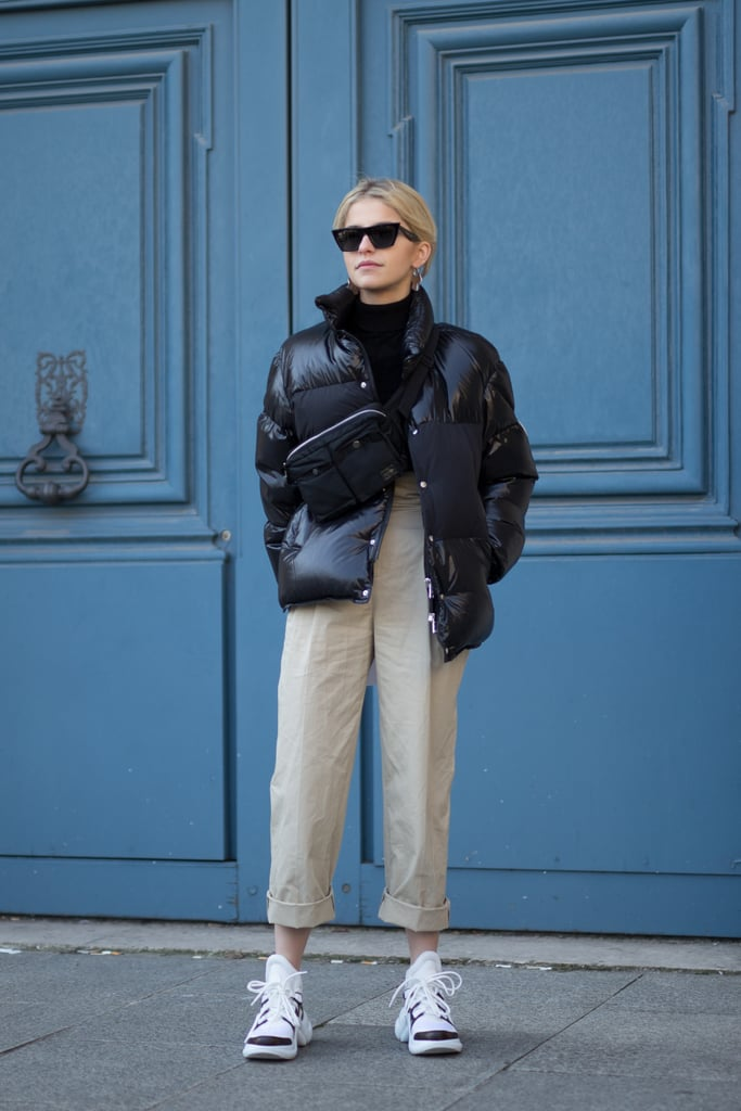 A Black Puffer Jacket, Khaki Trousers, Cross Body Bag, and Dad Sneakers