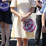 Kate Middleton, en route to Tuvalu, donned a daisy-eyelet dress in the pretty shade of pastel lemon by a yet-to-be-discovered independent designer. She complemented the look with her Stuart Weitzman sandal wedges and a colorful fan.