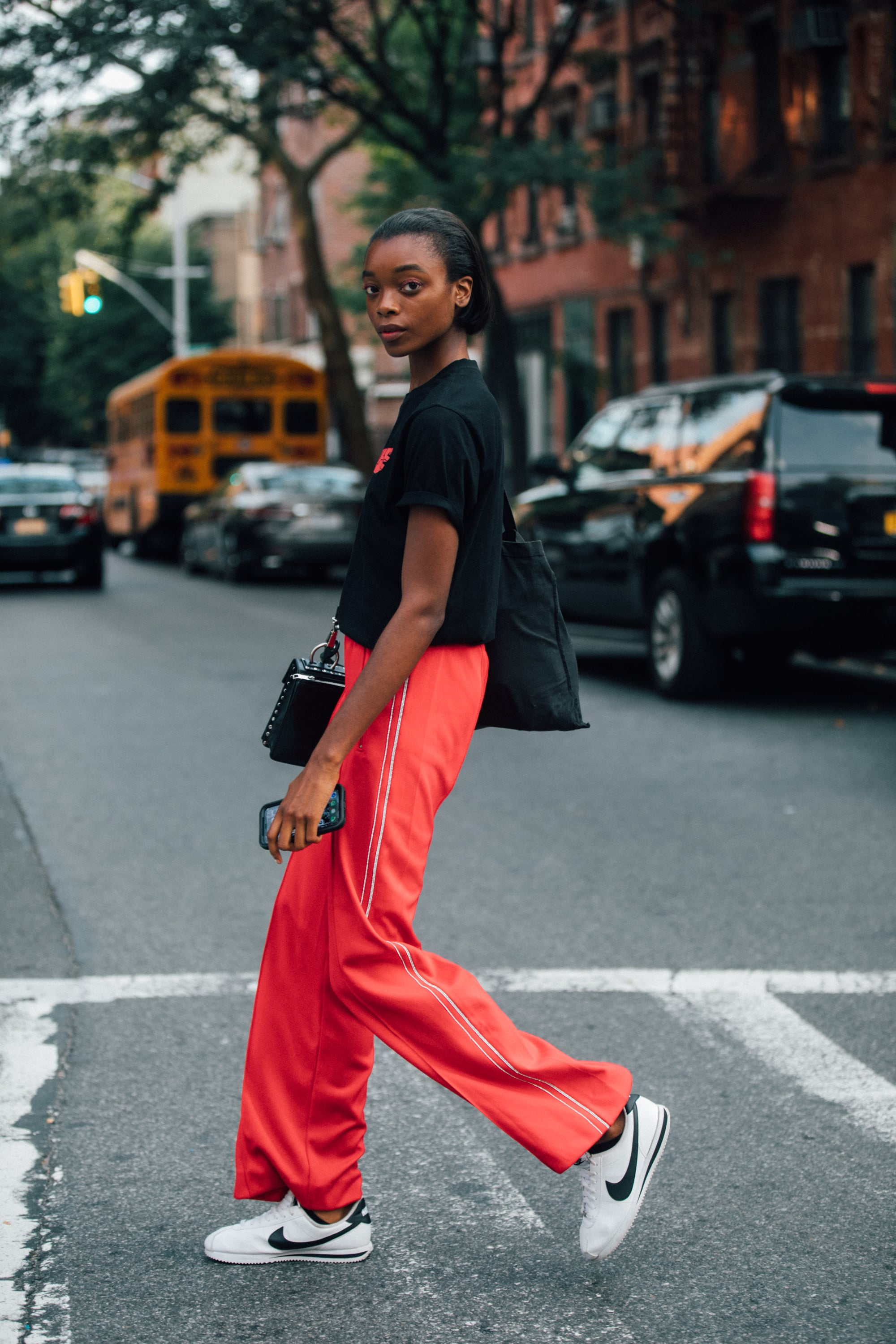 NEW YORK, NY - SEPTEMBER 6: Model Olivia Anakwe wears a black t-shirt, red pants, and white Nike sneakers during New York Fashion Week Spring/Summer 2019 on September 06, 2018 in New York City.