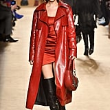 At Roberto Cavalli wearing a red trench coat and minidress.