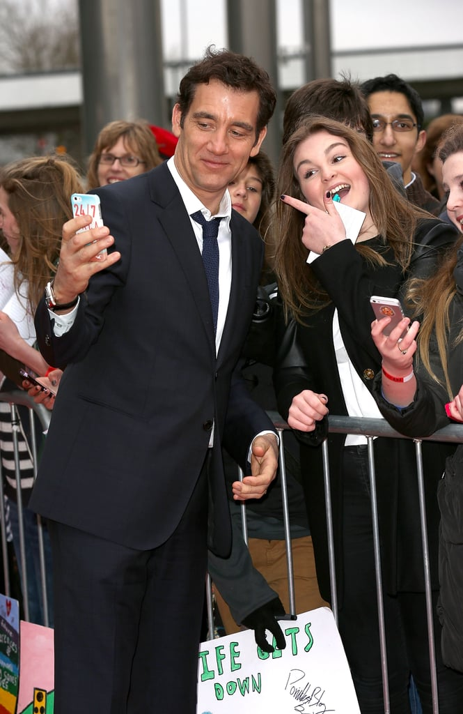 Clive Owen snapped a fan selfie at a charity event in London on Friday.
