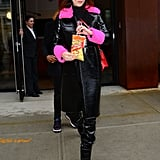 Enjoying a bag of Flamin' Hot Cheetos while wearing a black patent leather coat with pink furry accents. She finished her look off with Alchimia Di Ballin's Daphne puffer booties and a Prada bag.