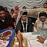Indonesian groom Rudiyanto holds the hand of his bride's father during the wedding ceremony.