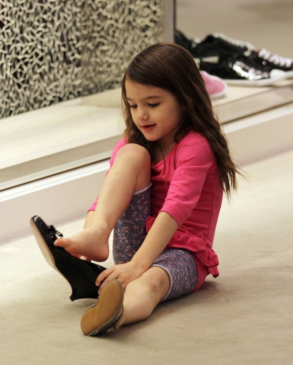 Suri Cruise entertained herself by trying on mommy-sized shoes while out shopping at Holt Renfrew with Katie Holmes and a couple friends in Vancouver yesterday. The tot is known to sport kitten heels of her own sometimes, a look that Lauren Conrad thinks only Suri can pull off. Katie checked out the selection as well, but only Suri tested out sparkly pumps for size. The girls are in Canada while Tom continues shooting Mission Impossible: Ghost Protocol in the city. Katie and Suri visited him on set on Friday night amid the news that Katie's History Channel miniseries The Kennedys will not be broadcast in the US. Katie still landed the cover of Elle to help promote the project and in the interview she once again talked up her four-year-old daughter's style sense. There's a chance that The Kennedys will air on another network and it will be shown internationally, though apparently the famous family itself might be behind it being pulled  in the first place.