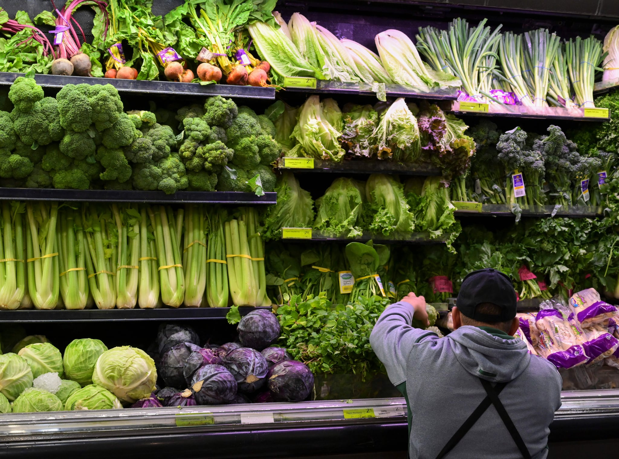 A produce worker stocks shelves near romaine lettuce (top shelf centre) at a supermarket in Washington, DC on November 20, 2018. - US health officials warned consumers not to eat any romaine lettuce and to throw away any they might have in their homes, citing an outbreak of E. coli poisoning. The Centres for Disease Control and Prevention (CDC) issued the warning against all Romaine lettuce just two days before the Thanksgiving holiday, when American families gather and feast together. (Photo by Andrew CABALLERO-REYNOLDS / AFP)        (Photo credit should read ANDREW CABALLERO-REYNOLDS/AFP/Getty Images)