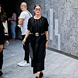 """Even in """"basic"""" black, Olivia is a trendsetter. With a statement belt and flats, everything from the proportions to the add-ons felt fresh."""