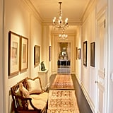 Beautiful molding, hardwood floors, and elegant lighting fill the hallway.
