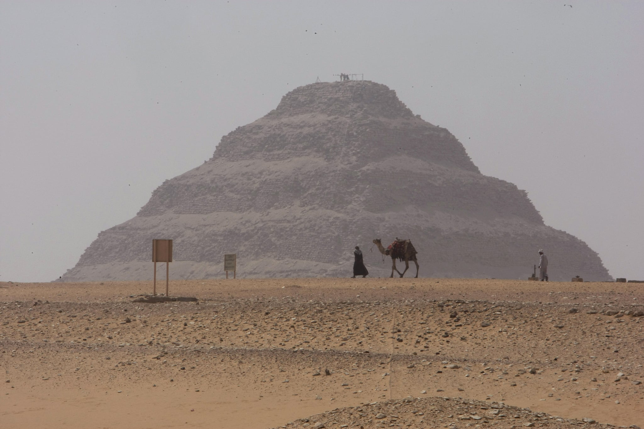 """A man walks with his camel on a foggy day past the Step Pyramid of Sakkara, located in the same region as the """"Headless Pyramid."""